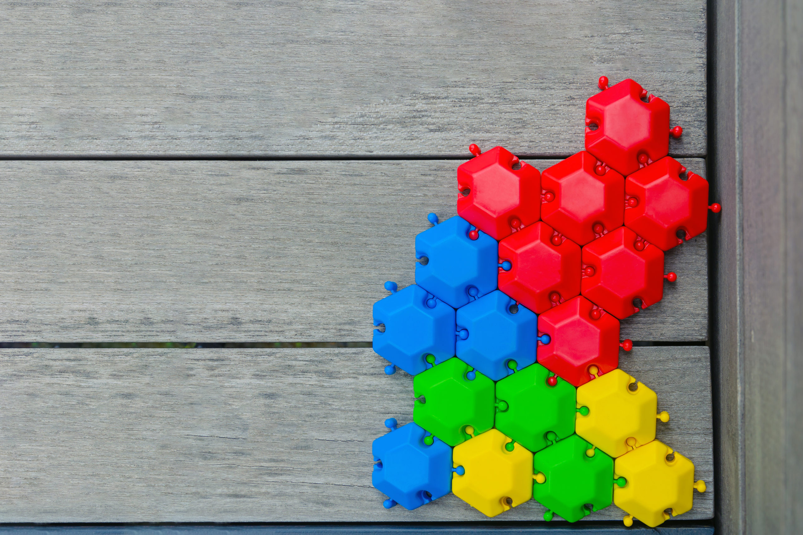 Game,Puzzle,Of,Multi-colored,Hexagons,Assembled,On,A,Wooden,Gray